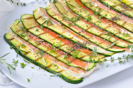 Grilled zucchini slices marinated with olive oil and herbs, served with fine Italian ham on a white plate