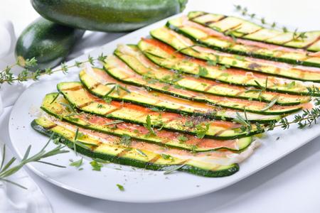 Grilované kukuřičné plátky marinované olivovým olejem a bylinkami, podávané s jemnou italskou šunkou na bílém talíři
