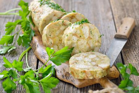 Krájený houskový knedlík, perfektní příloha pro pečeně nebo proužky masa s omáčkou, podávaná na dřevěné desce Reklamní fotografie