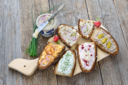 Hearty snack on farmhouse bread served on an old wooden table Reklamní fotografie - 89328028