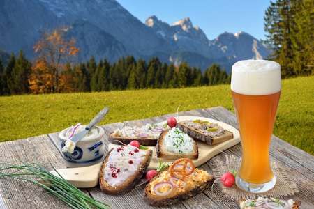 Hearty snack on farmhouse bread served with a fresh yeast on a wooden table in the Bavarian Alps