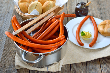Hot debreziner sausages on a wooden table with fresh rolls and spicy mustard