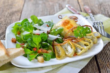 Gebraden Zwabische vleesravioli (ook wel 'Maultaschen') geserveerd met veldsla met croutons, spek en Parmezaanse kaas