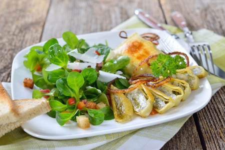 Gebratene schwäbische Fleischravioli (auch Maultaschen genannt), serviert mit Feldsalat mit Croutons, Speck und Parmesan