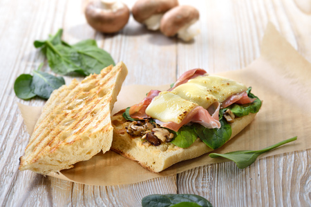 Street food: Hot panini with Spanish serrano ham and spaghetti leaves topped with grated cheese served on a wooden background Banque d'images