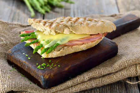 Street food: Hot panini served with ham and green asparagus topped with served cheese on a wooden background Banque d'images