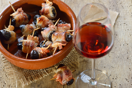 Delicious Spanish tapas: Fried prunes wrapped in bacon served with Portuguese port wine Reklamní fotografie - 94765124