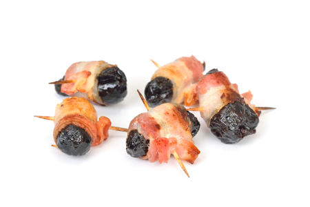 Delicious Spanish tapas on white background: Fried prunes wrapped in bacon