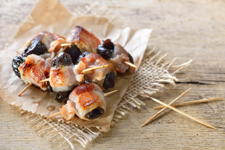 Delicious Spanish tapas: Fried prunes wrapped in bacon Reklamní fotografie - 94817304