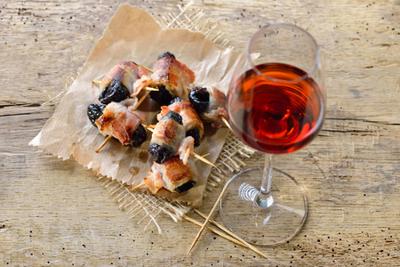 Delicious Spanish tapas: Fried prunes wrapped in bacon served with Portuguese port wine Reklamní fotografie - 94751430
