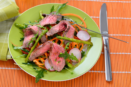 Mixed spring salad with roasted asparagus and medium fried beef steak cut into strips Reklamní fotografie - 95301196