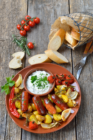 Spanish meal: Baked hot chorizo sausages with rosemary vegetables and mediterranean herb curd Stock Photo