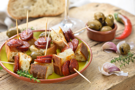 Spanish pinchos: Fried spicy chorizo sausage on roasted bread
