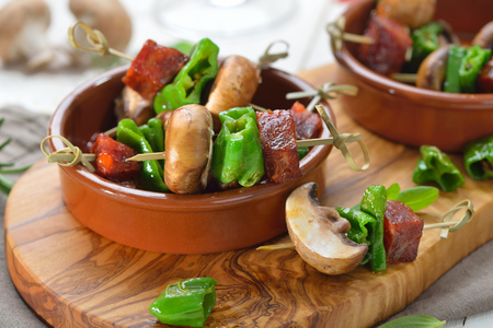 Spanish snack: pincho skewers with fried chorizo sausage, pimientos de padron and mushrooms