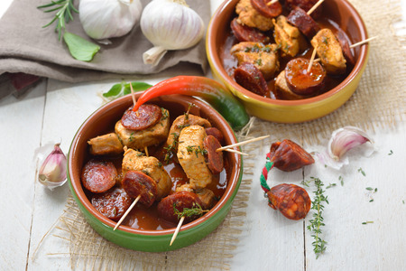 Hot Spanish snack: Braised pork fillet with fried slices of chorizo paprika sausage Stock Photo