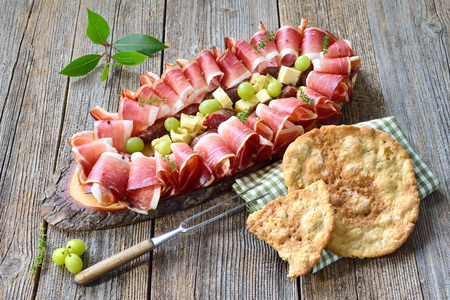Typical South Tyrolean snack with country bacon, salami and aged mountain cheese, served with local crunchy rye flat bread