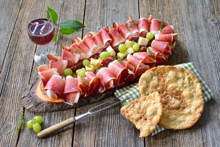 Typical South Tyrolean snack with country bacon, salami and aged mountain cheese, served with local red wine and crunchy rye flat bread
