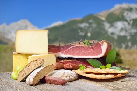 South Tyrolean specialties like bacon, sausages and cheese lying on a rustic table in front of mountains of the alps Reklamní fotografie