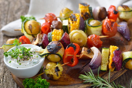 Grilled skewers with mixed vegetables served on a wooden cutting board with a vegan herb dip Reklamní fotografie