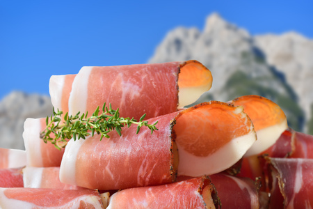 Sliced typical South Tyrolean bacon lying in the front of mountains of the alps