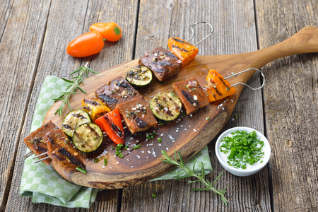 Vegan meal: grilled skewers with mixed vegetables served on a wooden cutting board with a herb sauce Reklamní fotografie