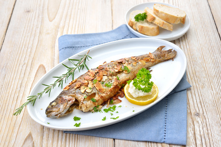 Fried trout with almonds, butter and creamed horseradish served on a white fish plate