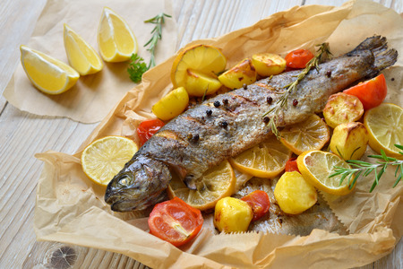 Baked lemon trout with oven-roasted rosemary potatoes and tomatoes, served on baking paper