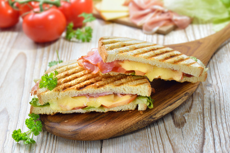 Grilled and pressed toast with smoked ham, cheese and tomato served on a wooden table