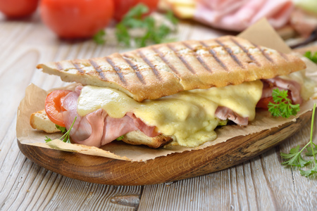Grilled and pressed baguette with smoked ham, cheese and tomato served on a wooden table Reklamní fotografie