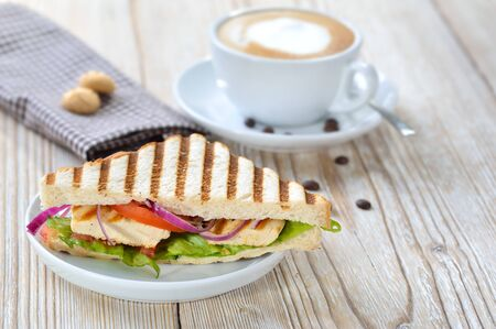 Pressed panini with grilled chicken breast fillet, tomatoes, onions and lettuce, served with a cappuccino Reklamní fotografie