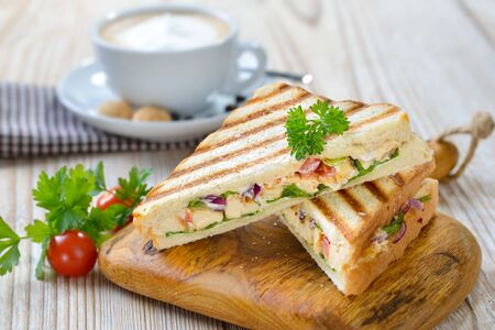 Pressed panini with grilled chicken breast fillet, tomatoes, onions and lettuce, served with a cappuccino 免版税图像