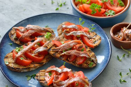 Spanish bar food: Grilled slices of bread with olive oil, herbs and spicy anchovy fillets