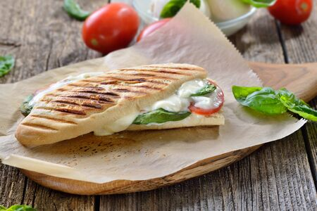 Pressed and toasted panini caprese with tomato, melted mozzarella and basil served on a wooden table