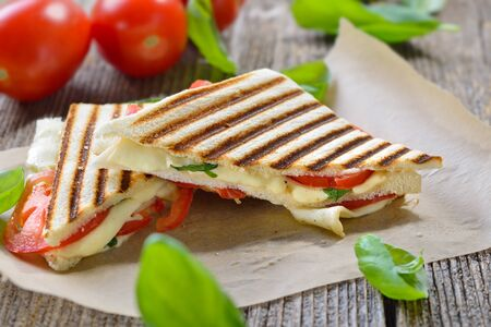 Pressed and toasted panini caprese with tomato, mozzarella and basil served on a wooden table Imagens