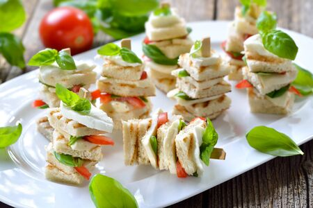 Toasted Italian bread with buffalo cheese and tomatoes on wooden skewers