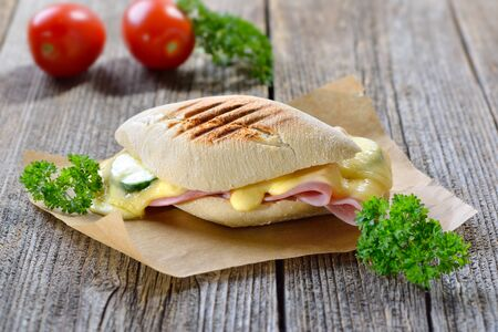Grilled and pressed panini with ham, melted cheese, cucumber and tomato served on a wooden table Imagens