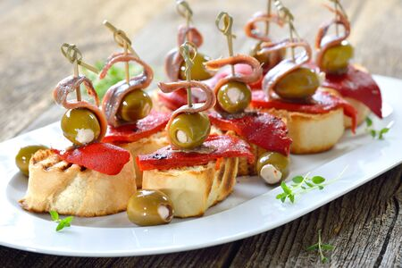 Spanish pinchos: Skewer snacks made with grilled bread with roasted and pickled peppers, stuffed with cream cheese and parmesan and on top delicious anchovy fillets Stock Photo