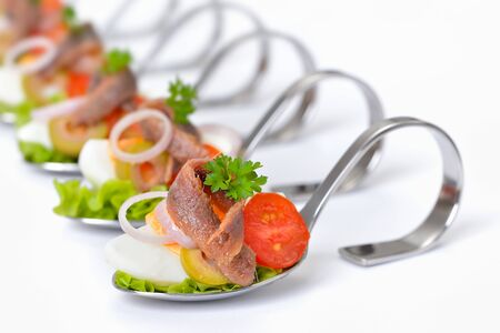 Fine fish appetizers with anchovy fillets and eggs on serving spoons set on a white background Zdjęcie Seryjne