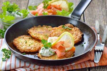 Crunchy potato pancakes with smoked salmon and sourcream with fresh green herbs served in an iron frying pan