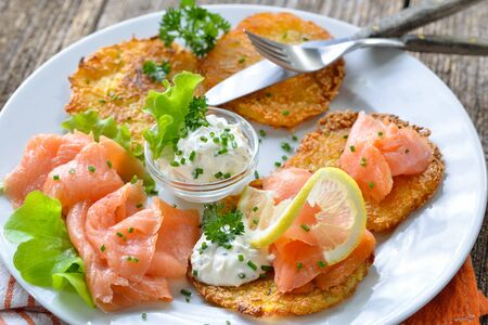 Crunchy potato pancakes with smoked salmon and sour cream with fresh green herbs