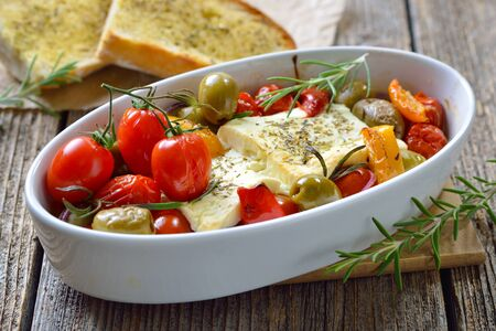 Warm Greek appetizer: Baked feta cheese with green olives, cherry tomatoes, peppers, onions and olive oil served with roasted herb baguette Reklamní fotografie
