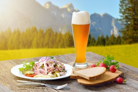 Hearty Bavarian sausage salad with cheese strips, pickles and rustic farmhouse bread served with a cool wheat beer in the background Stock Photo