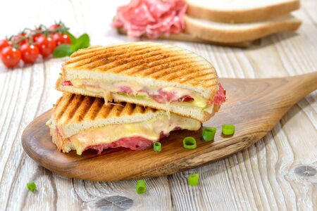 Grilled and pressed toast with Serrano salami, cheese, tomato and iceberg served on a wooden table