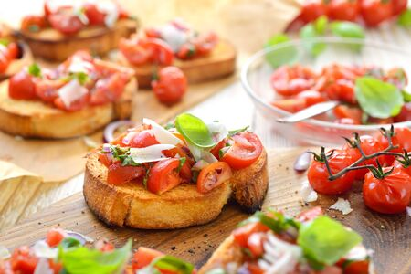 Warm Italian bruschetta: Crispy baked Italian ciabatta bread with cherry tomatoes, basil and parmesan cheese, served as an appetizer Stock Photo