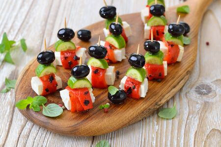 Greek appetizers: Feta cheese skewers with grilled and pickled red peppers, snack cucumbers and black olives, served as decorative finger food starters