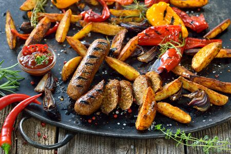 Grilled vegan soy sausages with hot sauce, potato wedges and vegetables