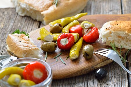 Greek snack: Cherry peppers and chillies stuffed with cream cheese, served with olives and fresh pita bread