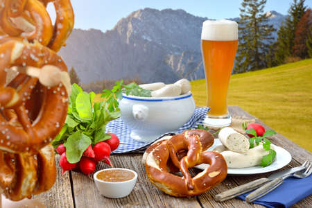 Hearty Bavarian breakfast with veal sausages, fresh pretzels and a wheat beer outside in the nature near Garmisch-Partenkirchen Reklamní fotografie