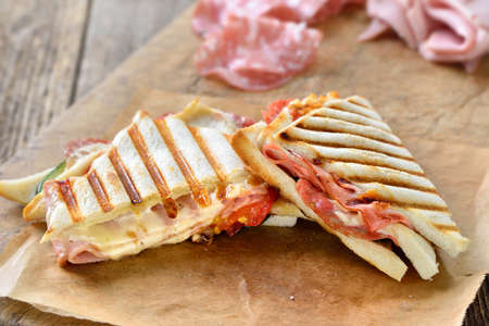 Pressed double panini with Italian salami, ham and cheese served fresh from the contact grill on sandwich paper