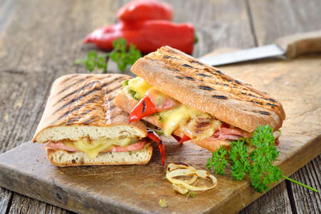 Grilled Italian ciabatta bread with ham, cheese and vegetables served on a wooden cutting board 版權商用圖片
